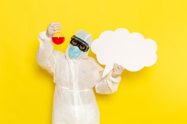 Вид спереди научный сотрудник мужского пола в специальном защитном костюме, держащий фляжку с красным раствором и большим белым знаком на светло-желтом столе