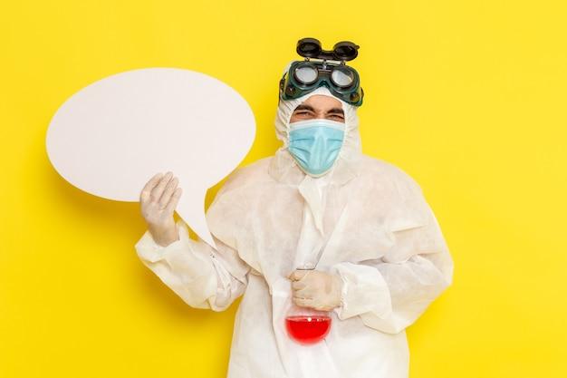Вид спереди мужского научного работника в специальном защитном костюме, держащего фляжку с красным раствором и белым знаком на светло-желтой поверхности