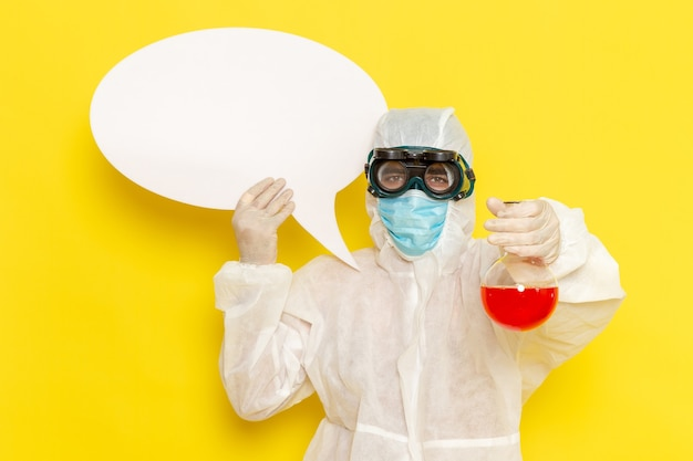 Вид спереди мужского научного работника в специальном защитном костюме, держащего фляжку с красным раствором и белым знаком на желтом столе