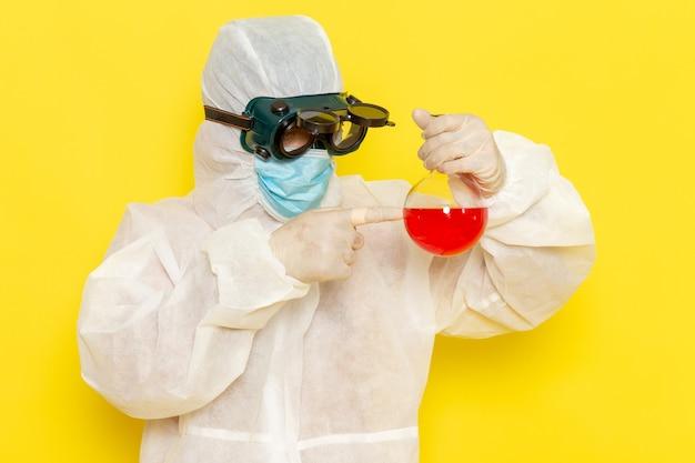 Вид спереди научный сотрудник мужского пола в специальном защитном костюме, держащий колбу с красным раствором на желтой поверхности