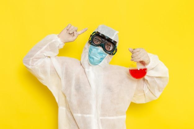 Вид спереди научный сотрудник-мужчина в специальном защитном костюме, держащий фляжку с красным раствором, позирует на светло-желтом столе