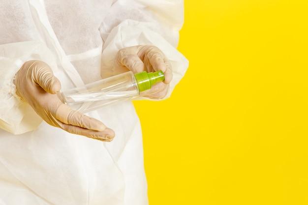 밝은 노란색 표면에 스프레이 플라스크를 들고 특수 보호 복에 전면보기 남성 과학 노동자