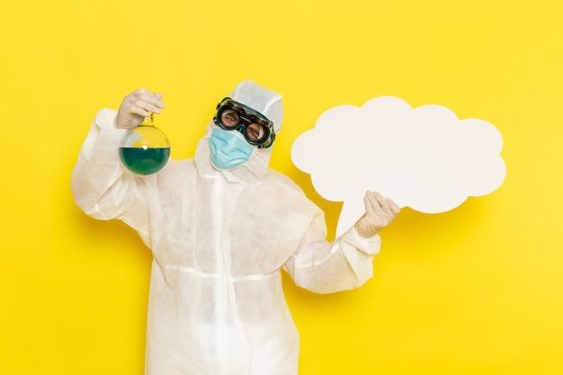 녹색 솔루션 및 노란색 책상에 큰 흰색 기호 플라스크를 들고 특별한 정장에 전면보기 남성 과학 노동자
