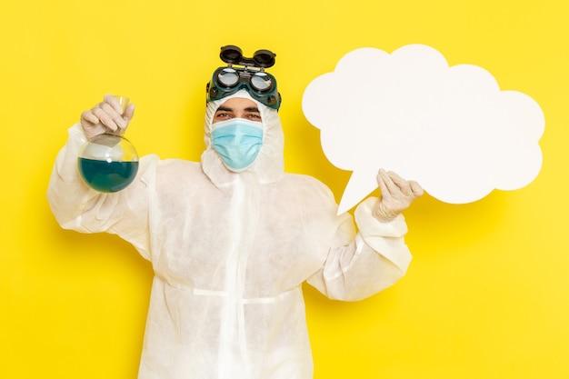 Вид спереди научный сотрудник мужского пола в специальном костюме, держащий фляжку с зеленым раствором и большой белый знак на желтом столе