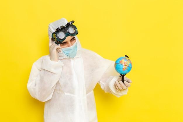 노란색 책상에 작은 지구 생각을 들고 특별한 정장에 전면보기 남성 과학 노동자