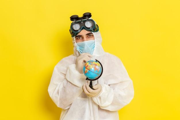 노란색 책상에 작은 지구본을 들고 특수 소송에서 전면보기 남성 과학 노동자