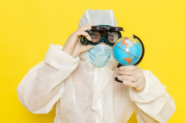 黄色い机の上でそれを観察している小さな丸い地球を保持している特別なスーツの正面図男性科学者