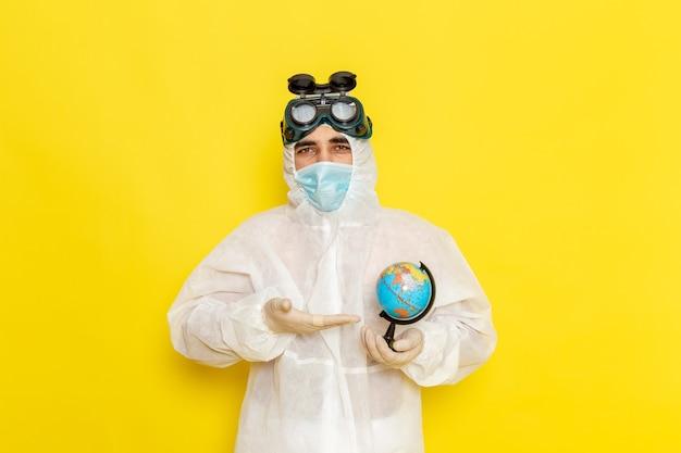 黄色い机の上に小さな丸い地球を保持している特別なスーツの正面図男性科学者