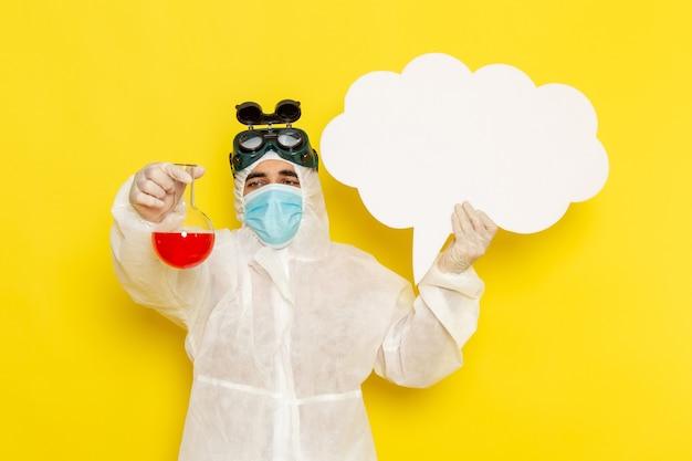 Operaio scientifico maschio vista frontale in vestito protettivo speciale che tiene boccetta con soluzione rossa grande segno bianco sullo scrittorio giallo
