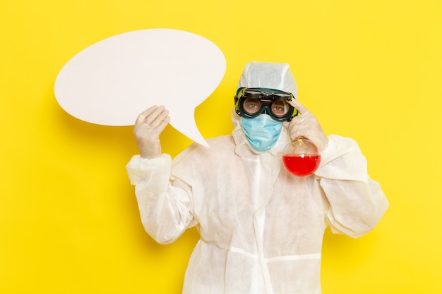 Front view male scientific worker in special protective suit holding flask with red solution and white sign on yellow desk