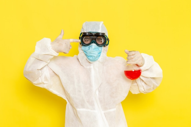 Front view male scientific worker in special protective suit holding flask with red solution on yellow surface