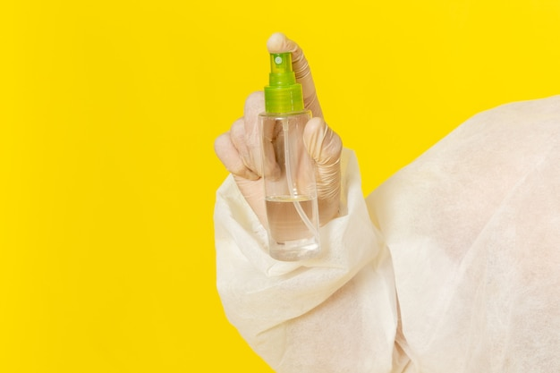 Front view male scientific worker in special protective suit holding spray on light-yellow surface