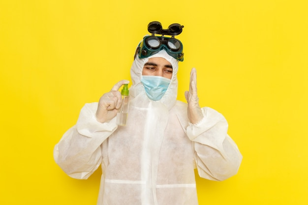 Front view male scientific worker in special protective suit holding spray using it on yellow desk