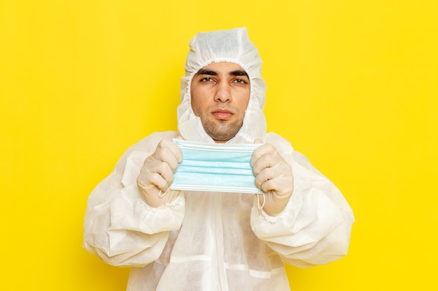 Front view of male scientific worker in special protective suit taking off his mask on light-yellow wall