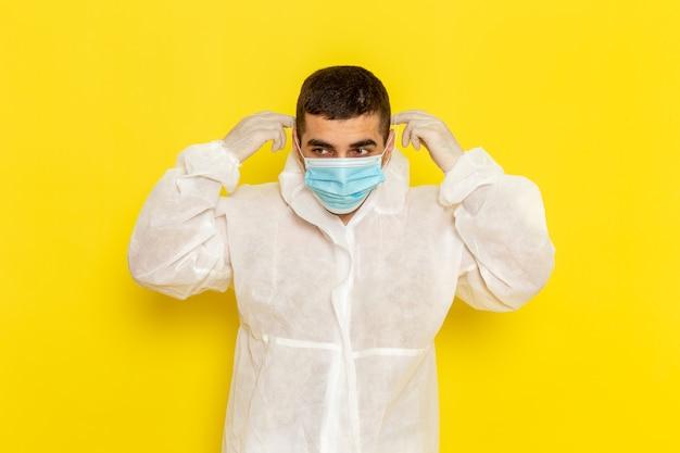 Vista frontale del lavoratore scientifico maschio in tuta protettiva speciale che indossa la sua maschera sulla parete gialla