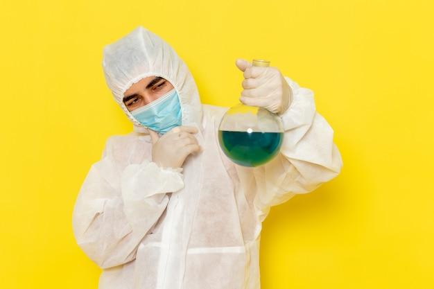 Vista frontale del lavoratore scientifico maschio in tuta protettiva speciale con maschera che tiene il pallone pensando sulla parete gialla
