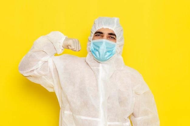 Vista frontale del lavoratore scientifico maschio in vestito bianco protettivo speciale con la maschera che flette sul pericolo di colore di chimica scientifica del lavoratore di scienza dello scrittorio giallo chiaro