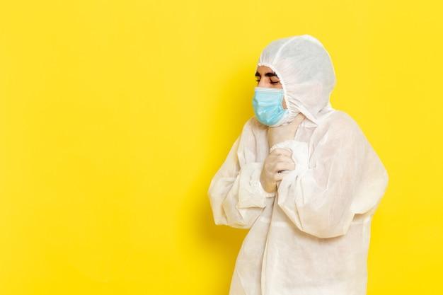 Vista frontale del lavoratore scientifico maschio in vestito bianco protettivo speciale e con la maschera che ha problemi alla gola sulla parete gialla