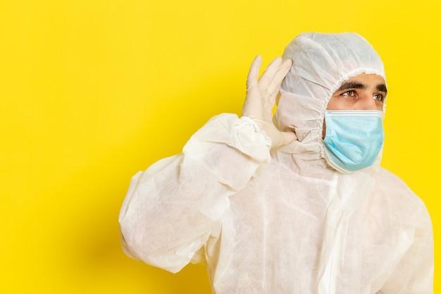 Vista frontale del lavoratore scientifico maschio in vestito bianco protettivo speciale e con la maschera che prova a sentire sulla parete gialla chiara