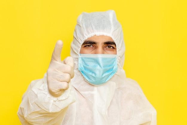 Vista frontale del lavoratore scientifico maschio in abito bianco protettivo speciale con maschera sterile minaccia sulla parete gialla