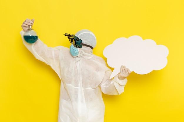Operaio scientifico maschio di vista frontale in vestito speciale che tiene boccetta con soluzione verde e grande cartello bianco su superficie gialla