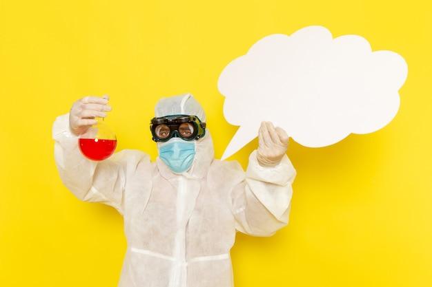 Operaio scientifico maschio di vista frontale in vestito speciale che tiene boccetta con soluzione rossa e grande cartello bianco sullo scrittorio giallo