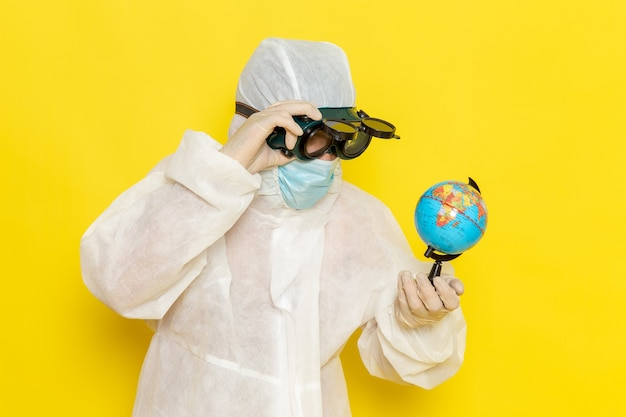 Front view male scientific worker in special suit holding little round globe on yellow desk