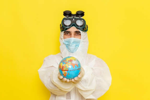 Front view male scientific worker in special suit holding little round globe on yellow floor