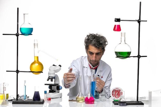 흰색 배경에 샘플 및 솔루션을 들고 전면보기 남성 과학자 코로나 바이러스 건강 연구소 covid