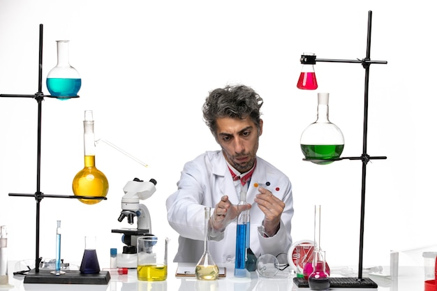 흰색 책상에 샘플 및 솔루션을 들고 전면보기 남성 과학자 코로나 바이러스 건강 연구소 covid