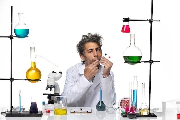 Scienziato maschio di vista frontale che tiene i campioni davanti al tavolo con soluzioni sul laboratorio di salute del coronavirus della scrivania bianca covid