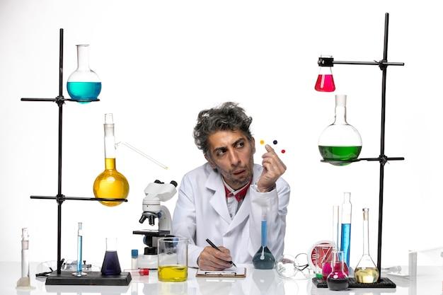 흰색 배경에 솔루션 테이블 앞에 샘플을 들고 전면보기 남성 과학자 코로나 바이러스 건강 연구소 covid