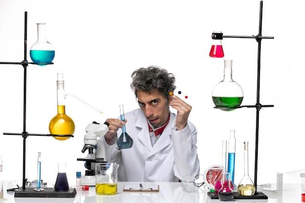밝은 흰색 배경에 솔루션 테이블 앞에서 샘플을 들고 전면보기 남성 과학자 코로나 바이러스 건강 연구소 covid