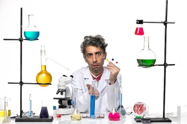 Scienziato maschio di vista frontale che tiene campioni e soluzione sul laboratorio di salute del coronavirus della scrivania bianca covid