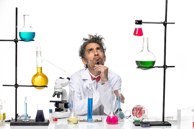 Scienziato maschio di vista frontale che tiene campioni su sfondo bianco coronavirus lab covid- salute