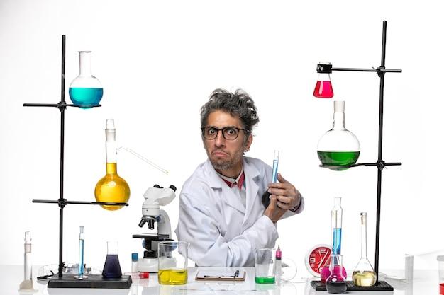 Вид спереди ученый-мужчина в медицинском костюме, держащий синий раствор на белом фоне, лаборатория коронавируса, здоровье, covid