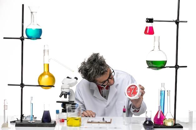 明るい白の背景に時計を保持している医療スーツの正面図男性科学者化学健康covid-labウイルス