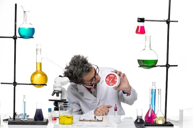 白い背景の化学covidウイルスの健康に時計を保持している医療スーツの正面図男性科学者