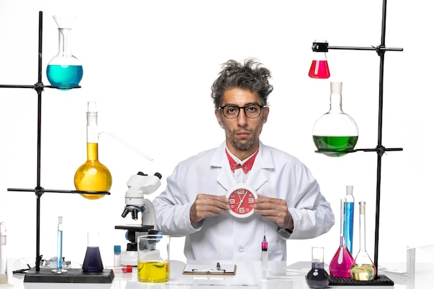 Вид спереди ученый-мужчина в медицинском костюме, держащий часы на белом фоне, вирус химии, здоровье, лаборатория covid