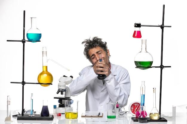Вид спереди ученый-мужчина в медицинском костюме, держащий фляжку с раствором на белом фоне, лаборатория коронавируса, здоровье, covid