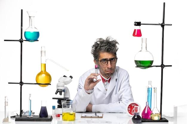 白い背景の化学covid-labウイルスに注射を保持している医療スーツの正面図男性科学者