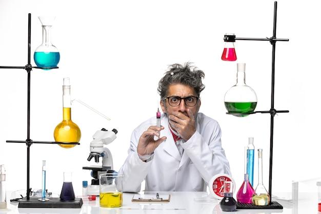 明るい白色の背景の化学covid-labウイルスに注射を保持している医療スーツの正面図男性科学者