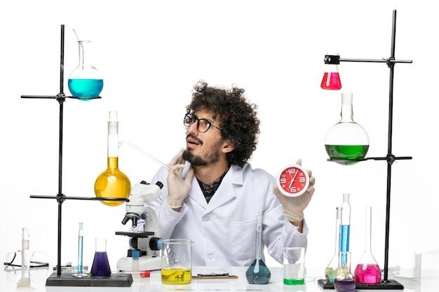 白いスペースに赤い時計を保持している医療スーツの正面図男性科学者