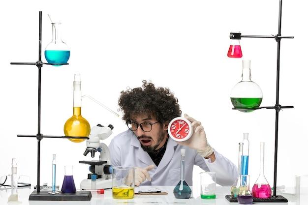 明るい白いスペースに赤い時計を保持している医療スーツの正面図男性科学者