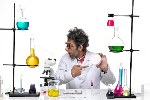 白い背景の化学covidラボウイルスの健康に赤い時計を保持している医療スーツの正面図男性科学者
