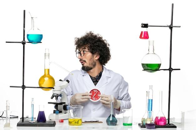 공백에 빨간 시계를 들고 의료 소송에서 전면보기 남성 과학자