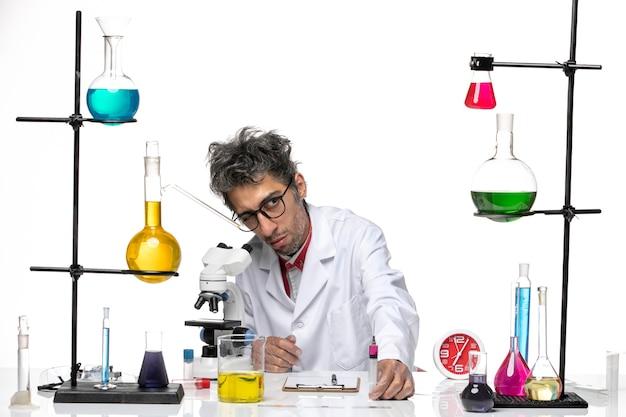白い背景のcovid-labウイルス健康化学で何かを見ている医療スーツの正面図男性科学者