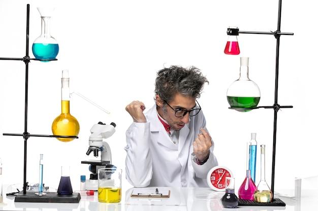 白い背景のcovidラボウイルス健康化学のソリューションとテーブルの前に座っている医療スーツの正面図男性科学者