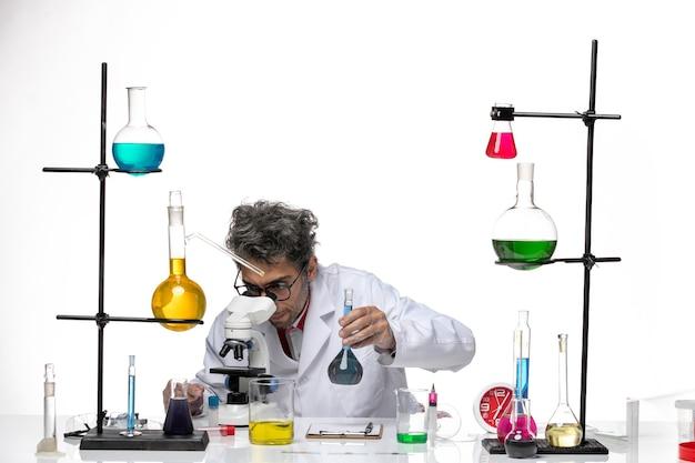Вид спереди ученый-мужчина в медицинском костюме с помощью микроскопа на белом фоне вирус здоровья лаборатории коронавирус