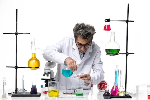 白い背景のラボウイルス健康化学コロナウイルスのさまざまなソリューションで作業している医療スーツの正面図男性科学者